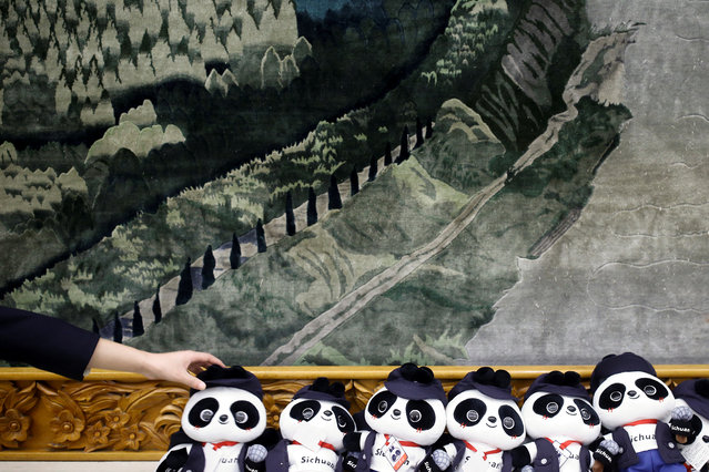 A man arranges Panda soft toys during a session of the Sichuan province on the second day of the 19th National Congress of the Communist Party of China at the Great Hall of the People in Beijing, China on October 19, 2017. (Photo by Thomas Peter/Reuters)