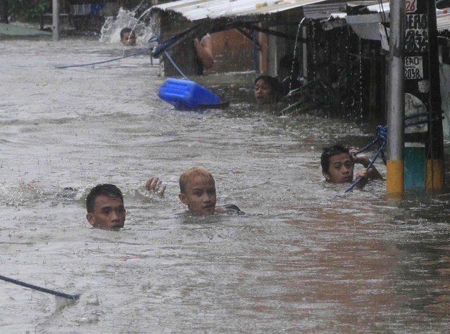 Residents swim in a flooded area to get to another street after tropical storm Fung-Wong battered metro Manila September 19, 2014. (Photo by Erik De Castro/Reuters)