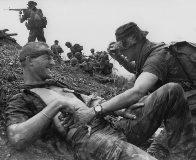 South Vietnamese and Montagnard troops attack in an uphill battle near Ha Thanh, some 325 miles northeast of Saigon, September 2, 1968, as an American medic attends a wounded U.S. Special Forces soldier. The GI was wounded during the battle as an Allied strike force sought to retake an outpost which had been overrun by the Viet Cong on Friday. The strike force retook the outpost. (Photo by AP Photo)
