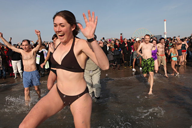A woman takes part in the annual Coney Island Polar Bear Club New Year's Day swim by running into the ocean at Coney Island on January 1, 2011 in the Brooklyn borough of New York City. The Coney Island Polar Bear Club claims itself as the oldest winter bathing organization in the U.S. and attracts hundreds to the beach for the annual swim in the Atlantic Ocean. (Photo by Andrew Burton)