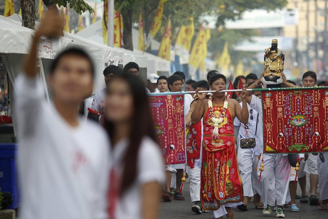A couple takes pictures of themselves as devotees of the Chinese Bang Neow Shrine take part in a procession celebrating the annual vegetarian festival in Phuket September 29, 2014. (Photo by Damir Sagolj/Reuters)