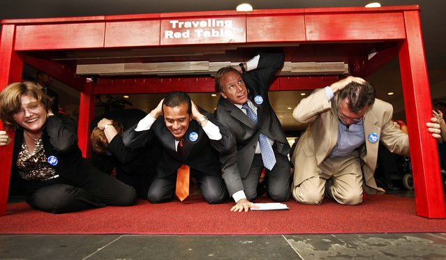 """Dr. Lucile Jones with the U.S. Geological Survey, Los Angeles Mayor Antonio Villaraigosa, Paul Schulz CEO of the American Red Cross and Richard Katzr dropped under the red table to """"drop, cover, and hold on"""" during the Great California ShakeOut earthquake drill at Union Station October 18, 2012. (Photo by Al Seib/Los Angeles Times)"""