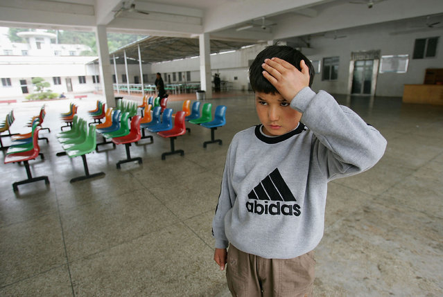 Maimaiti Aili, a 13-year old boy from China's Xinjiang Uygur Autonomous Region, holds his head after being hit at an assistance center February 23, 2005 in Shenzhen, Guangdong Province, China. (Photo by Cancan Chu/Getty Images)