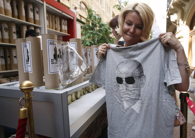 A woman holds up T-shirt with an image depicting Russia's President Vladimir Putin, at GUM department store in central Moscow, August 11, 2014. (Photo by Maxim Zmeyev/Reuters)
