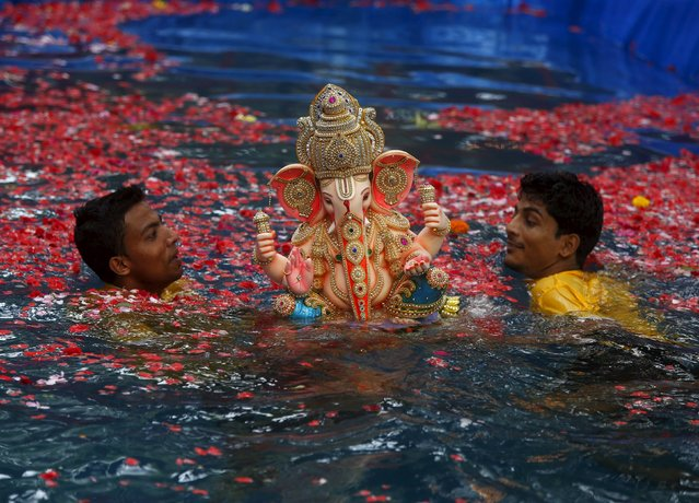 Volunteers carry an idol of the Hindu elephant god Ganesh, the deity of prosperity, in a pond for its immersion during the ten-day-long Ganesh Chaturthi festival in Mumbai, India, September 18, 2015. (Photo by Shailesh Andrade/Reuters)