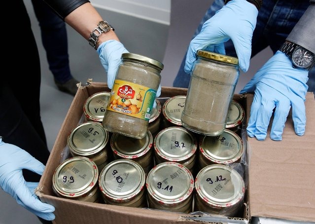 Criminal experts display glasses filled with heroin at the headquarters of the federal police in Wiesbaden, Germany, Thursday, October 9, 2014. German authorities have seized 330 kilograms (728 pounds) of heroin worth an estimated 50 million euros (US$63 million) that smugglers brought to Europe hidden in a shipment of cucumbers and garlic from Iran. (Photo by Michael Probst/AP Photo)