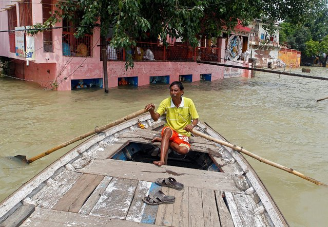 A man rows a boat through a street flooded by water from the banks of the river Ganga, in Allahabad, India, August 26, 2016. (Photo by Jitendra Prakash/Reuters)