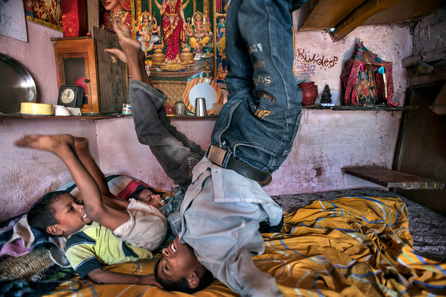 Three boys play on the bed their entire family shares. From the left are Ajit Kumar, 5, Dilip Kumar, 9, and Kuldeep Kumar, 10. The bed occupies their entire living space. Their home is located on a garbage dump. Kusum Pahari slum, South Delhi, India. (Photo by Renée C. Byer/Living on a Dollar a Day)