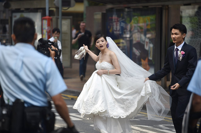 A wedding couple speak to police officers as they try to leave the area of a pro-democracy protest in the Admiralty district of Hong Kong on October 14, 2014. (Photo by Pedro Ugarte/AFP Photo)