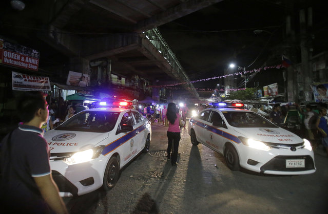 In this June 8, 2016 file photo, police cars block a street as they enforce an overnight curfew for minors in Manila, Philippines. Even before he takes his oath of office on Thursday, Philippine President-elect Rodrigo Duterte's vow to kill drug criminals appear already being rolled out. At least dozens of suspected drug criminals have either been killed in shootouts with police or mysteriously found dead on the streets in what some fear is a portent of things to come. (Photo by Aaron Favila/AP Photo)