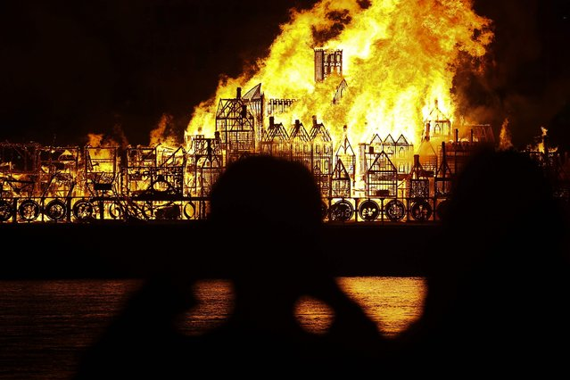 A replica of 17th-century London on a barge floating on the river Thames burns in an event to mark the 350th anniversary of the Great Fire of London, in London on September 4, 2016. A giant replica of 17th-century London was set ablaze on the Thames in the city to mark the 350th anniversary of the devastating Great Fire of London. The 1666 inferno destroyed most of the walled inner city dating back to Roman times – a bustling, congested maze of tightly-packed wooden houses. It forced London to rebuild anew from the ashes. (Photo by Justin Tallis/AFP Photo)