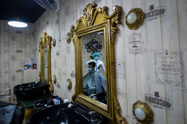 A barber wearing protective cloths gives a haircut to a client at a barber shop amid concerns over the spread of the COVID-19 coronavirus, in Dhaka on July 7, 2020. (Photo by Munir Uz Zaman/AFP Photo)