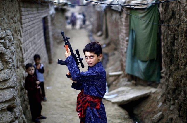 An Afghan refugee boy poses with a plastic rifle as he and other children celebrate the first day of the Eid al-Fitr festival, which marks the end of the Muslim fasting month of Ramadan, in a slum on the outskirts of Islamabad, Pakistan, August 20, 2012. Muslims around the world are celebrating Eid al-Fitr, marking the end of Ramadan, the Muslim calendar's ninth and holiest month during which followers are required to abstain from food and drink from dawn to dusk. (Photo by Muhammed Muheisen/AP Photo)