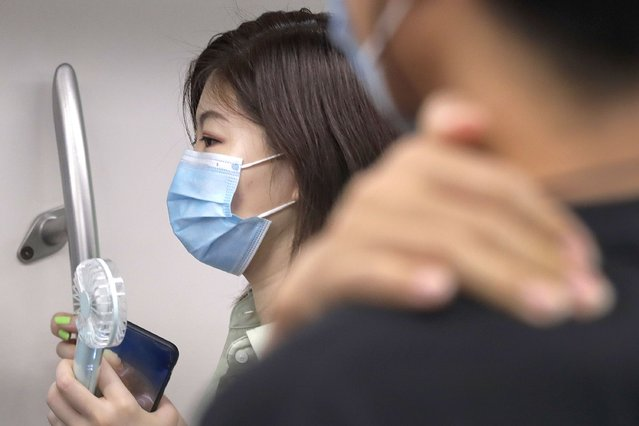 A woman wearing a face mask to protect against the new coronavirus uses an electric fan to cool herself as she rides in a subway train in Beijing, Wednesday, July 29, 2020. China reported more than 100 new cases of COVID-19 on Wednesday as the country continues to battle an outbreak in Xinjiang. (Photo by Andy Wong/AP Photo)