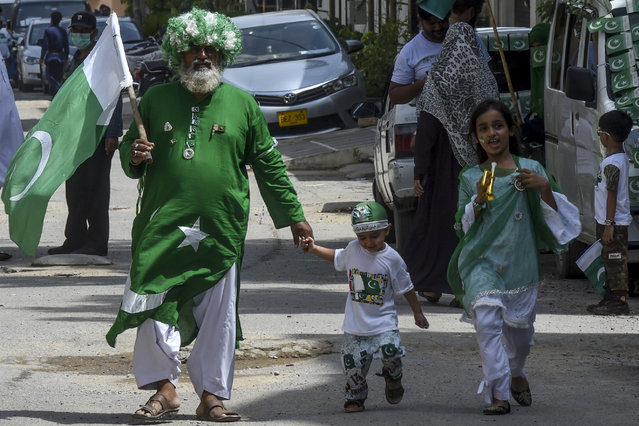A man wearing an outfit designed as the Pakistani national flag walks along with his children during the Independence Day celebrations in Karachi on August 14, 2020. (Photo by Asif Hassan/AFP Photo)