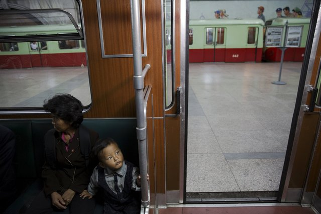 A boy sits next to a woman inside a train that stopped at a subway station visited by foreign reporters during a government organised tour in Pyongyang, North Korea October 9, 2015. (Photo by Damir Sagolj/Reuters)