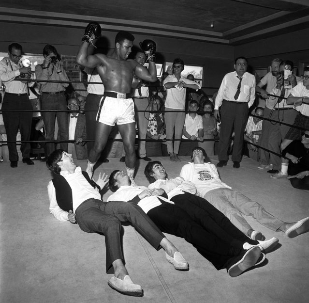 """Cassius Clay poses in a mock victory over the Beatles, at his training camp in Miami, Fla., 1964. (Clay changed his name to Muhammad Ali after his win against Sonny Liston). (Photograph from """"Harry Benson: Persons of Interest"""" by Harry Benson, published by powerHouse Books)"""