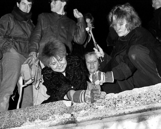 Berliners take a hammer and chisel to a section of the Berlin Wall in front of the Brandenburg Gate after the opening of the East German border was announced on November 9, 1989. (Photo by Fabrizio Bensch/Reuters)