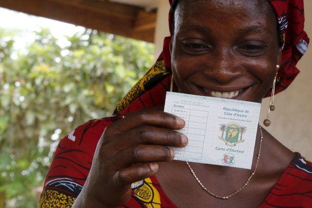 A woman smiles as she receeived  her electoral card  in GBAGBA, Bingerville  district, Abidjan, Ivory Coast October 15, 2015. (Photo by Thierry Gouegnon/Reuters)