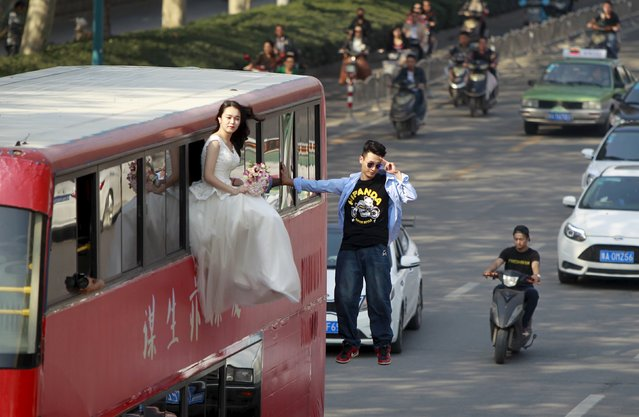 Magician Lei Xin (R) is seen suspended outside a double-deck bus, next to a woman in a wedding gown, as they participate in a performance on a street in Zhengzhou, Henan province, China, October 15, 2015. (Photo by Reuters/Stringer)