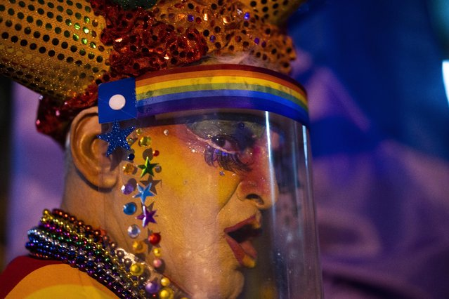 A person wearing a face mask amid of new coronavirus pandemic dances during the Diversity parade in Montevideo, Uruguay, Friday, September 25, 2020. The event is held every year to raise awareness and fight against discrimination based on sexual identity and orientation. (Photo by Matilde Campodonico/AP Photo)