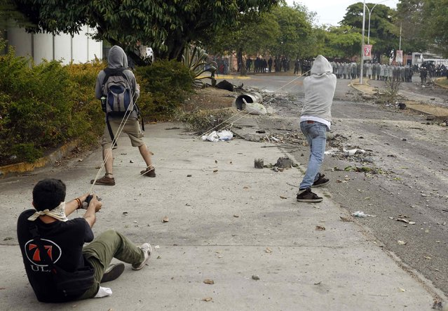 Demonstrators use a slingshot against the National Guard during a protest in San Cristobal, in this February 27, 2014 file photo. Following a couple of days of riots in Caracas, we decided to travel to the Venezuelan city of San Cristobal to photograph the conflict there. In the afternoon, I was told of clashes between anti-government protests and the National Guard, but barricades blocking almost every street made it extremely difficult to commute from one place to another, even by motorbike. (Photo and caption by Carlos Garcia Rawlins/Reuters)