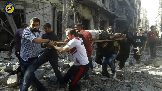 In this photo provided by the Syrian Civil Defense group known as the White Helmets, Syrians carry a victim after airstrikes by government helicopters on the rebel-held Aleppo neighborhood of Mashhad, Syria, Tuesday September 27, 2016. With diplomacy in tatters and a month left to go before U.S. elections, the Syrian government and its Russian allies are using the time to try and recapture the northern city of Aleppo, mobilizing pro-government militias in the Old City and pressing ahead with the most destructive aerial campaign of the past five years. (Photo by Syrian Civil Defense White Helmets via AP Photo)