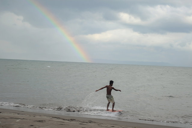 A rainbow appears while a resident surfing by the beach in the coastal village of San Jose, on November 07, 2014 in Tacloban, Philippines. November 8 will mark one year since Typhoon Haiyan devastated central Philippines, killing nearly 8,000 people and leaving millions displaced.  (Photo by Ezra Acayan/Barcroft Media)