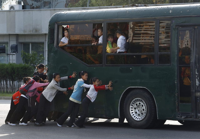 North Korean children push a bus in a street in Pyongyang, North Korea Thursday, Sept. 20, 2012. (Photo by Vincent Yu/AP Photo)