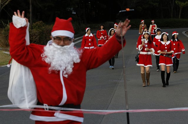 People dressed in Santa costumes participate in the Tokyo Santa Run as a man runs towards the finish line, at a park in Tokyo December 6, 2014. (Photo by Yuya Shino/Reuters)