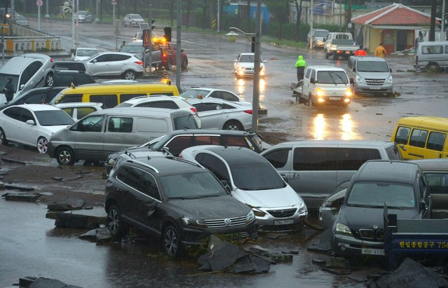 Cars damaged by flood waters caused by Typhoon Chaba are seen along a street in the southern island of Jeju on October 5, 2016. The typhoon hit the South Korean resort island of Jeju early on October 5, bringing heavy rains that flooded streets, forced flight cancellations and disrupted power to thousands of homes. More than 25,000 houses on the island of Jeju had their power supply disrupted, the Yonhap news agency reported, while Busan city announced the closure of 900 schools. (Photo by AFP Photo/Yonhap)