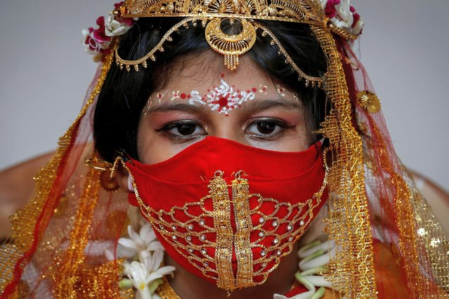 Sarayna Biswas, 6, wearing a face mask and dressed as Kumari wearing gold, takes part in a ritual during the Durga Puja festival celebrations at a pandal, or a temporary platform, amidst the outbreak of the coronavirus disease (COVID-19), in Kolkata, India, October 24, 2020. (Photo by Rupak De Chowdhuri/Reuters)