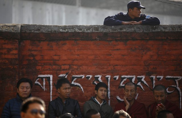 A police officer looks through the wall as Tibetans take part in a function organised by the Tibetan Refugee Community in Nepal, commemorating the 25th Anniversary of the Nobel Peace Prize conferment to exiled Tibetan spiritual leader Dalai Lama and the 66th International Human Rights Day in Kathmandu December 10, 2014. (Photo by Navesh Chitrakar/Reuters)