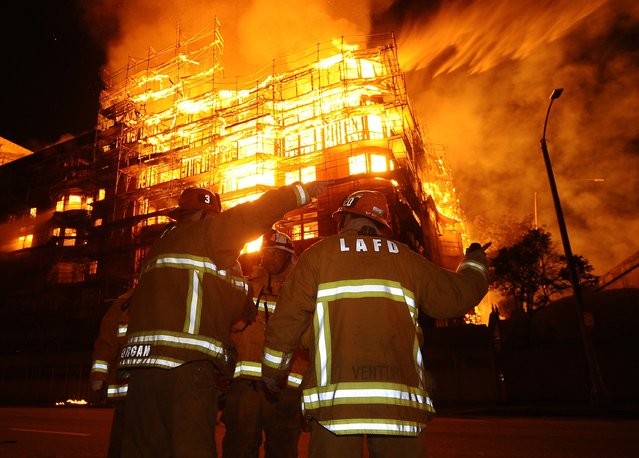 Los Angeles city firefighters battle a massive fire at a seven-story downtown apartment complex under construction in Los Angeles, California December  8, 2014. Over 250 firefighters battle the early morning blaze which shutdown two major freeways the Los Angeles Fire Department and California Highway Patrol said. (Photo by Gene Blevins/Reuters)