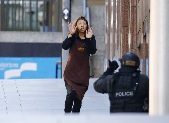 A hostage runs towards a police officer outside Lindt cafe, where other hostages are being held, in Martin Place in central Sydney December 15, 2014. Two more hostages have run out of the cafe at the center of a siege in Sydney, Australia's largest city, according to a Reuters witness at the site. (Photo by Jason Reed/Reuters)