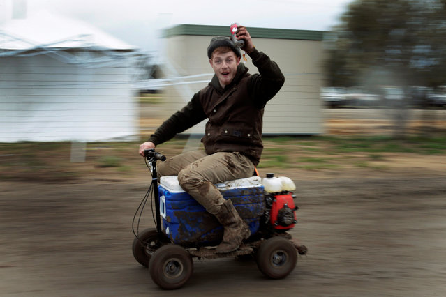 """Sheep shearer Chris Kermond from Ballarat in the Australian state of Victoria rides a motorised """"esky"""" or drink cooler, while drinking a can of pre-mixed rum and cola at the Deni Ute Muster in Deniliquin, New South Wales, September 29, 2016. (Photo by Jason Reed/Reuters)"""