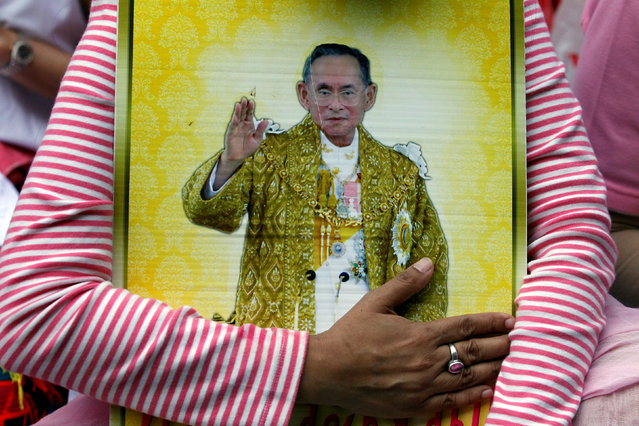 A well-wisher hugs a portrait of Thailand's King Bhumibol Adulyadej at the Siriraj hospital where he is residing in Bangkok, Thailand, October 13, 2016. (Photo by Chaiwat Subprasom/Reuters)