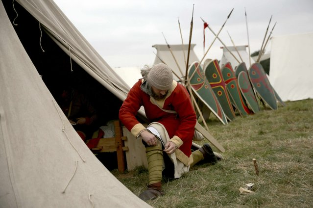 A re-enactor adjusts his costume before a re-enactment of the Battle of Hastings, commemorating the 950th anniversary of the battle, in Battle, Britain October 15, 2016. (Photo by Neil Hall/Reuters)