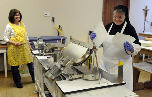 Sister Rebecca Leis (R) and lay worker Cindy Welch inspect a broken sheet of low-gluten alter bread during baking at the Benedictine Sisters of Perpetual Adoration monastery in Clyde, Missouri, December 18, 2014. (Photo by Dave Kaup/Reuters)