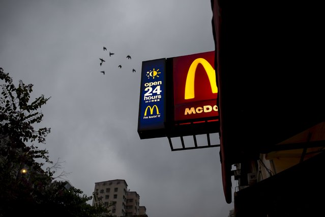 Birds fly past a sign of 24-hour McDonald's restaurant at sunrise in Hong Kong, China November 11, 2015. (Photo by Tyrone Siu/Reuters)