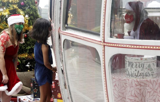 A girl visits a man dressed as Santa Claus inside an old cable car at Urca Hill near Pao de Acucar Mountain (Sugar Loaf Mountain) during a Christmas event in Rio de Janeiro, Brazil, December 5, 2020. (Photo by Ricardo Moraes/Reuters)