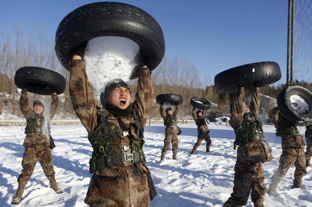 People's Liberation Army (PLA) soldiers pour snow from a tyre onto their head during a training session in Heihe, Heilongjiang province December 24, 2014. (Photo by Reuters/Stringer)