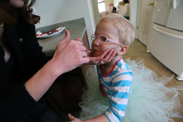 In this April 29, 2014 file photo, Moriah Barnhart, gives her cancer suffering three year old daughter Dahlia cannabis oil treatment with an oral syringe, at her home in Colorado Springs. (Photo by Brennan Linsley/AP Photo)