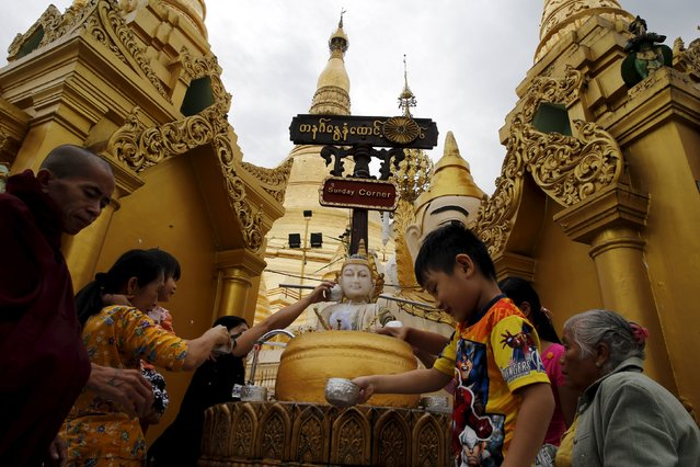 People take part in a religious ritual at Shwedagon Pagoda in Yangon, Myanmar, November 10, 2015. (Photo by Jorge Silva/Reuters)