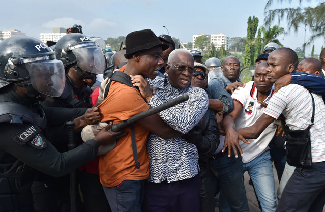 Ivory Coast' s riot police arrest Aboudramane Sangare (C) one of country' s opposition leaders during a protest against a referendum on the adoption of a new constitution that changes contentious rules on presidential eligibility on October 20, 2016 in Abidjan. .Current rules require both parents of presidential candidates to have been born in Ivory Coast. It was one of the factors that triggered violent unrest five years ago during contested elections won by President Alassane Ouattara. (Photo by Issouf Sanogo/AFP Photo)