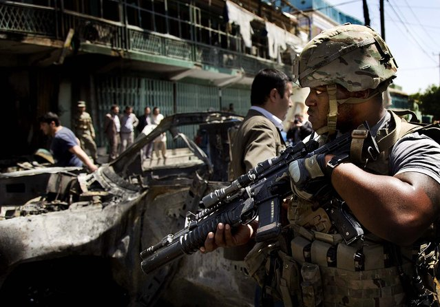 A U.S. soldier arrives at the scene where a suicide car bomber attacked a NATO convoy in Kabul, Afghanistan, on May 16, 2013. A Muslim militant group, Hizb-e-Islami, claimed responsibility for the early morning attack, killing many in the explosion, police and hospital officials said. The powerful explosion rattled buildings on the other side of Kabul and sent a pillar of white smoke into the sky. (Photo by Anja Niedringhaus/Associated Press)