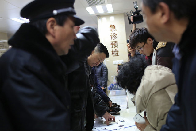 People try to identify their relatives at a hospital, from pictures of some of the victims of a stampede during a New Year's celebration on the Bund, central Shanghai January 1, 2015. (Photo by Aly Song/Reuters)