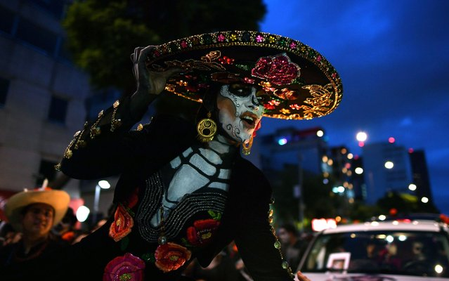 "A woman dressed as ""Catrina"" takes part in the ""Catrinas Parade"" along Reforma Avenue, in Mexico City on October 23, 2016. (Photo by Yuri Cortez/AFP Photo)"