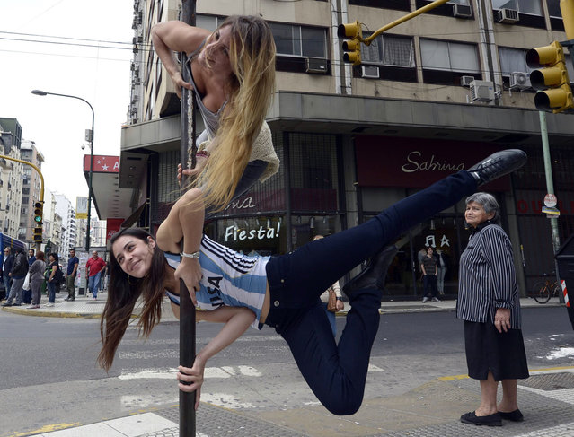Participants in the Pole Dance Argentina 2012 and Pole Dance South America 2012 competitions perform in downtown Buenos Aires on November 23, 2012 ahead of the contest to be held on November 24 and 26 in Buenos Aires. (Photo by Juan Mabromata/AFP Photo)