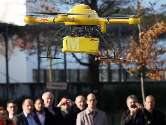 In this December 9, 2013 photo, a Deutsche Post DHL drone carrying a small parcel flies in front of journalists during a demonstration in Bonn, Germany. Germany's express delivery and mail company is testing a drone that could be used to deliver urgently needed goods to hard-to-reach places. The aircraft can carry up to 3 kilograms (6.6 pounds). (Photo by Oliver Berg/AP Photo/DPA)